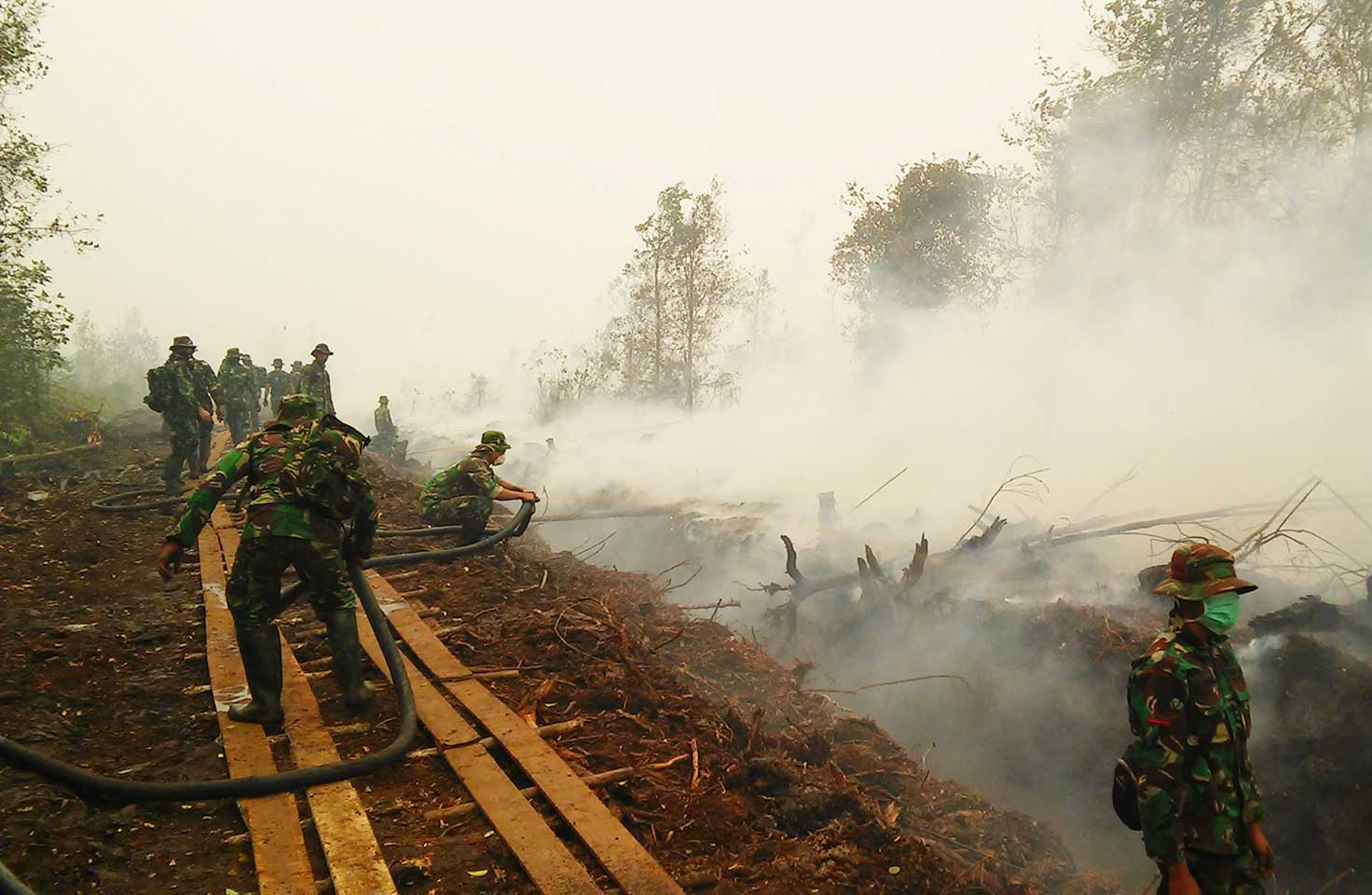 Photo of Indonesian military personnel fighting peat fire